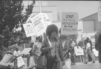 Jonathan Peter Jackson (face obscured by sign) walking with Angela Davis at march for the Soledad Brothers in Los Angeles, Calif., 1970.jpg